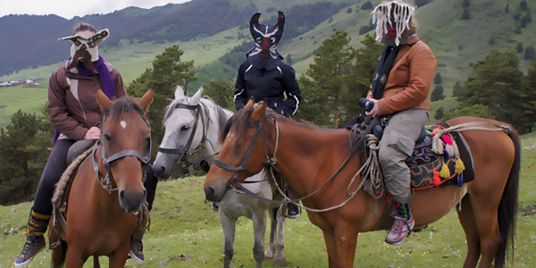 three artists wearing felt masks on horseback in a mountain setting